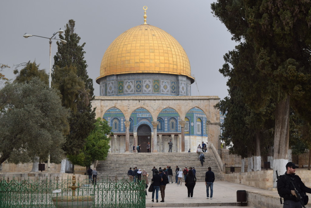 Temple Mount surrounded by pilgrims, stormy skies and armed guards.